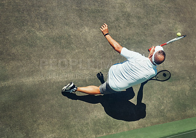 Buy stock photo High angle shot of a focused middle aged man playing tennis outside on a tennis court during the day