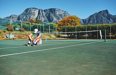 Buy stock photo Full length shot of a young male tennis player feeling tired and sitting down on a tennis court outdoors