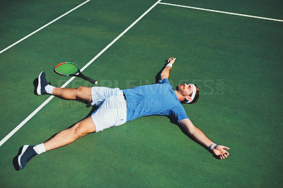 Buy stock photo Full length shot of a handsome young male tennis player lying down on a tennis court outdoors