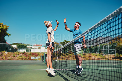 Buy stock photo Full length shot of two young tennis players giving each other a high five outdoors on the court
