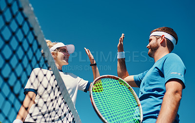 Buy stock photo Low angle shot of two young tennis players giving each other a high five outdoors on the court
