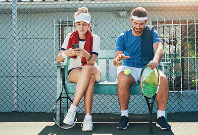 Buy stock photo Full length shot of two young tennis players sitting down and having a conversation together outdoors on the court