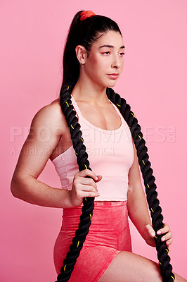 Buy stock photo Studio shot of a sporty young woman holding a battle rope around her neck against a pink background