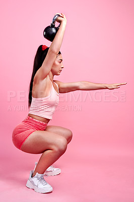 Buy stock photo Studio shot of a sporty young woman doing squats with a kettlebell against a pink background