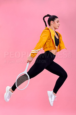 Buy stock photo Studio shot of a sporty young woman jumping with a tennis racket against a pink background