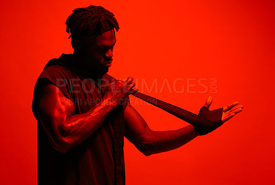 Buy stock photo Read filtered shot of a sporty young man wrapping his hands before boxing