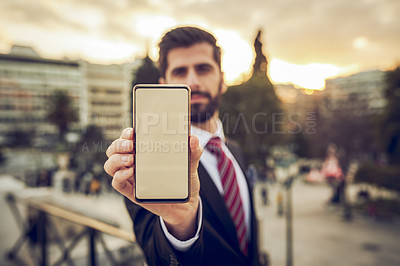 Buy stock photo Cropped portrait of a handsome young businessman showing off a smartphone while standing on a balcony in a foreign city