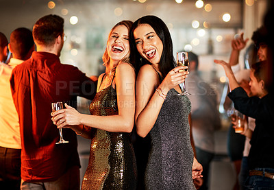 Buy stock photo Cropped shot of two cheerful young women having drinks while dancing on the dance floor of a club at night