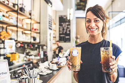 Buy stock photo Portrait of a cheerful young woman holding two coffee beverages to give to customers inside of a coffee shop during the day