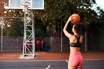 Buy stock photo Full length shot of an attractive young sportswoman standing alone on a basketball court and warming up with the ball