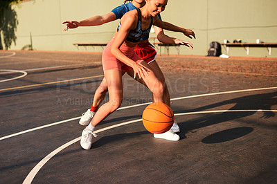 Buy stock photo Cropped shot of an attractive young sportswoman blocking her opponent during a basketball game during the day