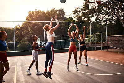 Buy stock photo Cropped shot of a diverse group of sportswomen playing a competitive game of basketball together during the day
