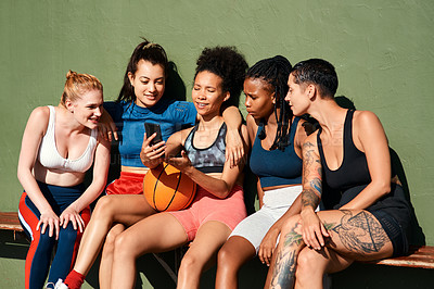 Buy stock photo Cropped shot of a diverse group of sportswomen sitting together after playing basketball and looking at a cellphone