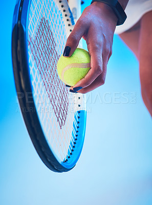 Buy stock photo Cropped shot of an unrecognizable young female tennis player getting ready to serve against a blue background