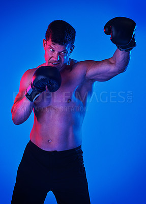 Buy stock photo Blue filtered shot of a sportsman wearing boxing gloves while posing in the studio