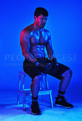Buy stock photo Blue filtered shot of a boxer sitting on a step ladder