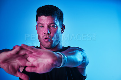 Buy stock photo Blue filtered shot of a sportsman stretching in the studio