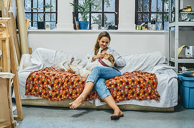 Buy stock photo Shot of a young woman relaxing with her dog on a sofa at home