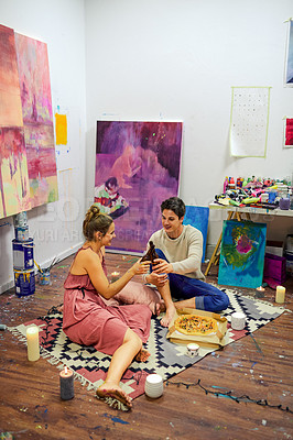 Buy stock photo Shot of a cheerful young couple having a celebratory toast with beer while having a date surrounded by candles and paintings inside of an art studio