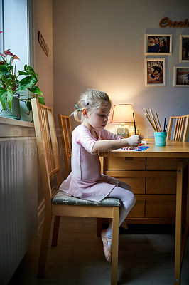 Buy stock photo Shot of a focused little girl painting a picture with paint brushes while being seated at a table inside during the day