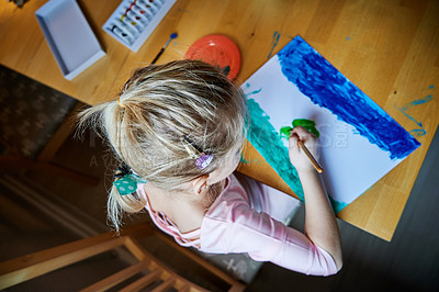 Buy stock photo High angle shot of a focused little girl making a picture using different types of art supplies while being seated at a table inside during the day