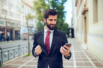 Buy stock photo Shot of a young businessman holding his fist in excitement while using a cellphone in the city