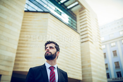 Buy stock photo Shot of a young businessman looking thoughtful while standing in the city
