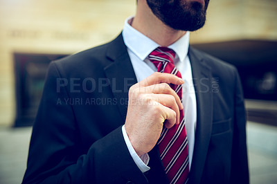 Buy stock photo Closeup shot of an unrecognisable businessman adjusting his tie in the city