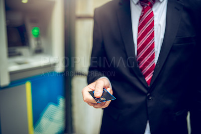 Buy stock photo Closeup shot of an unrecognisable businessman holding a credit card in front of an ATM