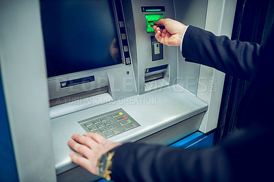 Buy stock photo Closeup shot of an unrecognisable businessman making a transaction at an ATM
