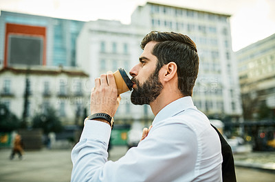 Buy stock photo Shot of a young businessman drinking coffee while out in the city