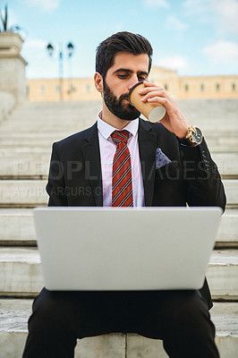 Buy stock photo Shot of a young businessman drinking coffee while using a laptop on a staircase in the city