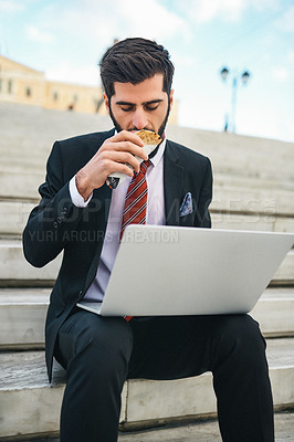 Buy stock photo Shot of a young businessman eating a pita sandwich while using a laptop in the city