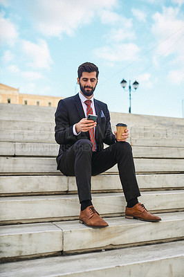 Buy stock photo Shot of a young businessman using a cellphone while drinking coffee on a staircase the city