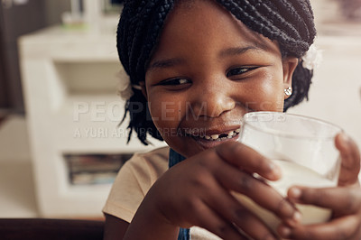Buy stock photo Cropped shot of an adorable little girl drinking a glass of milk at home