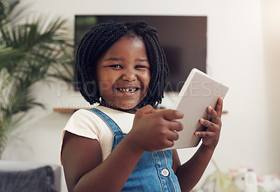 Buy stock photo Portrait of an adorable little girl having fun while using digital a tablet at home
