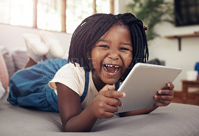 Buy stock photo Portrait of an adorable little girl having fun while using a digital tablet at home