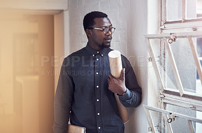 Buy stock photo Cropped shot of a handsome young male architect holding a scroll of blueprints while standing in a modern office