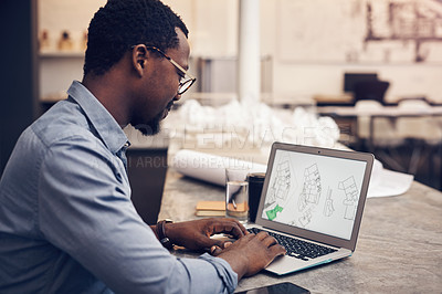 Buy stock photo Cropped shot of a handsome young male architect working on a laptop in a modern office