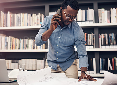Buy stock photo Cropped shot of a handsome young male architect taking a phonecall while working with blueprints in a modern office