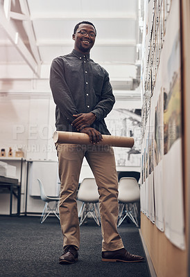 Buy stock photo Full length portrait of a handsome young male architect smiling while holding a scroll of blueprints in a modern office
