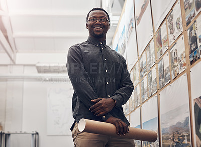 Buy stock photo Cropped portrait of a handsome young male architect smiling while holding a scroll of blueprints in a modern office
