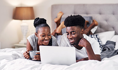 Buy stock photo Shot of a young couple using a laptop while relaxing on their bed