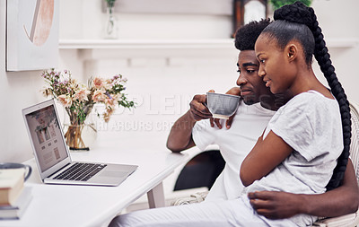 Buy stock photo Shot of a young couple using a laptop while sitting together at home