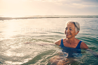 Buy stock photo Shot of a cheerful senior woman enjoying herself while swimming outdoors in the ocean