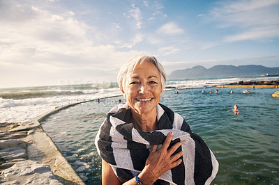 Buy stock photo Portrait of a cheerful senior woman covering herself with a towel after swimming outdoors in the ocean
