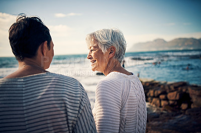 Buy stock photo Cropped shot of a senior woman bonding and spending time with her adult daughter at the beach