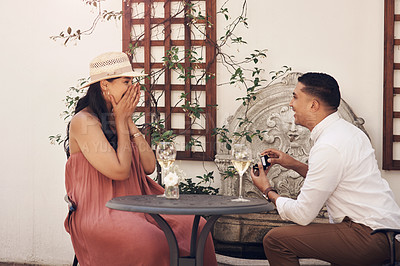 Buy stock photo Shot of a man proposing to his girlfriend while out on a date