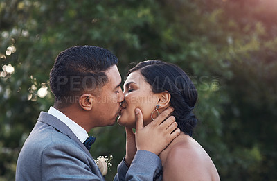 Buy stock photo Cropped shot of a young couple sharing a kiss on their wedding day