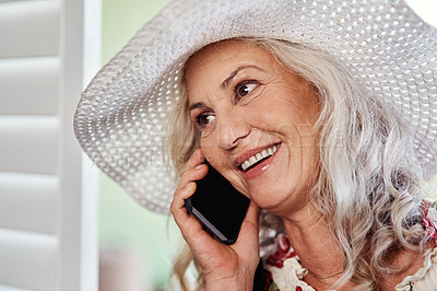 Buy stock photo Cropped shot of an attractive senior woman taking a phonecall while standing indoors at home